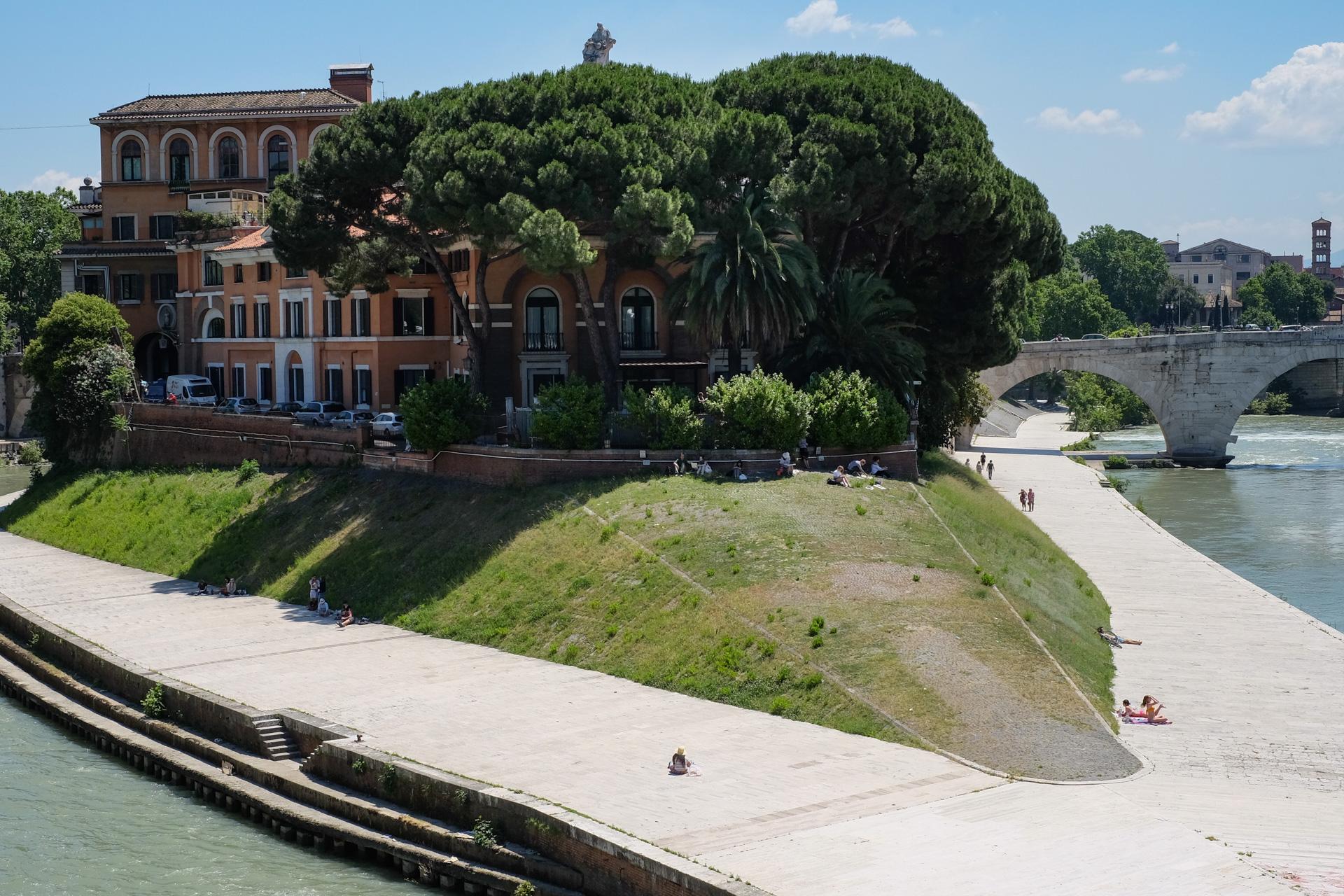 Maisema Tiber-joen varrelta, isot pinjat rakennuksen edessä