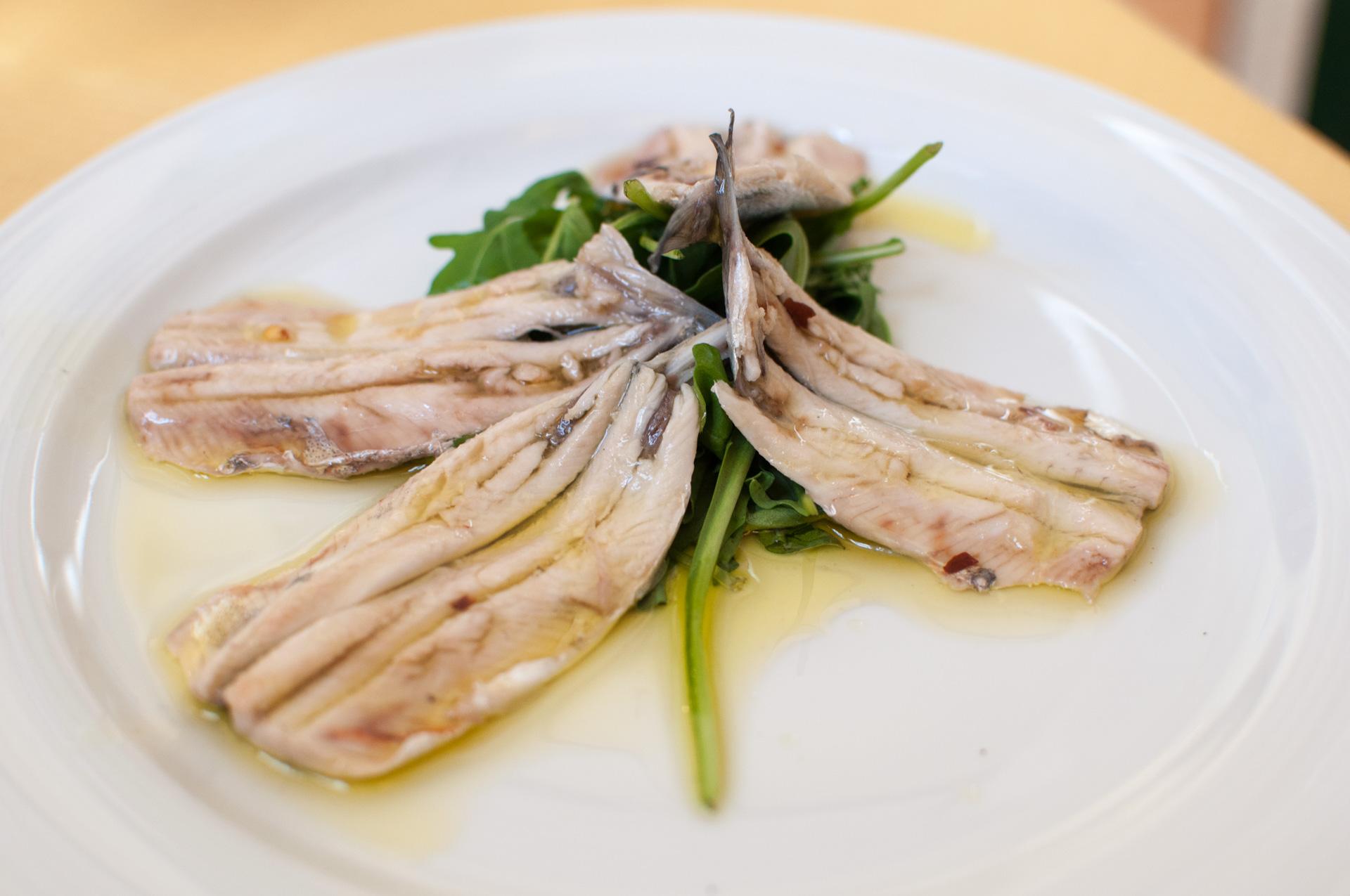 Ruodottomia sardellifileitä lautasella rucolan kanssa