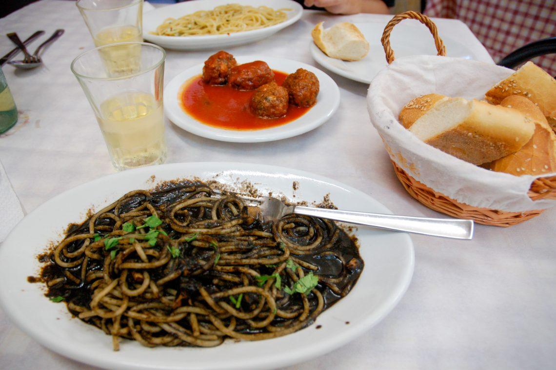 Mustekalan mustetta ja spagettia ravintolan pöydällä